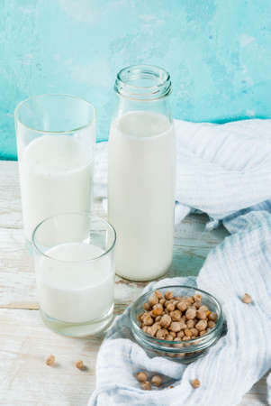 Vegan alternative food, soy non-dairy milk on light blue background, copy space