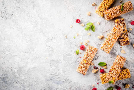 Healthy breakfast and snack concept, homemade granola bars with fresh raspberries, on grey stone stone background copy space  top view