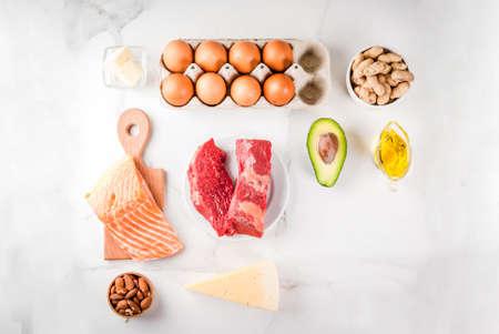 Concetto di dieta chetogenica a basso contenuto di carboidrati. Alimento sano ed equilibrato con alto contenuto di grassi sani. Dieta per cuore e vasi sanguigni. Ingredienti alimentari biologici, sfondo di marmo bianco, copia spazio vista dall'alto