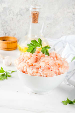 Raw chicken or turkey minced meat in white bowl,  with oil, spices and herbs on light background. Copy space vertical