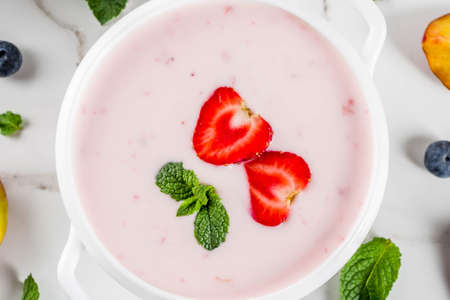 Summer healthy diet dinner, vegan food, dessert, various sweet creamy fruit & berry soups - strawberry, peach, blueberry, white marble background  copy space above close view