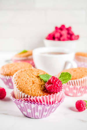 Sweet summer dessert, homemade baked muffin with raspberry jam, served with tea, fresh raspberries and mint. On a white marble table, copy space Stock Photo