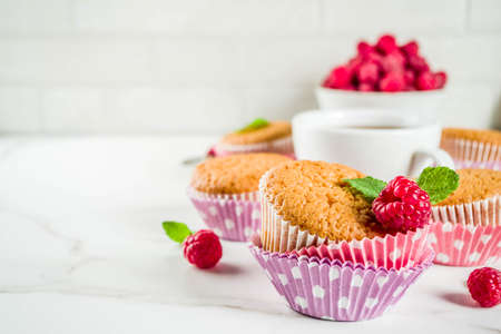 Sweet summer dessert, homemade baked muffin with raspberry jam, served with tea, fresh raspberries and mint. On a white marble table, copy space 版權商用圖片
