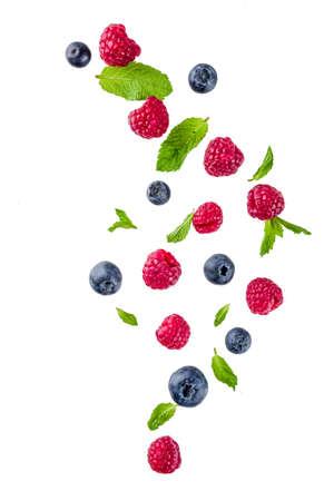 Diseño creativo, fondo, con bayas frescas, patrón simple sobre fondo blanco. Frambuesa, arándano, hojas de menta, rodajas de limón. Foto de archivo