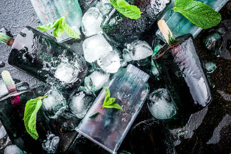 Trendy food, Asian vegan desserts, homemade ice cream popsicles with algae spirulina, served with mint in glasses with ice, dark rusty background copy space