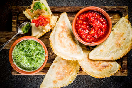 Latin American, mexican, chilean food. Traditional baked pastry empanadas with beef meat, two spicy sauces, dark rusty background copy space