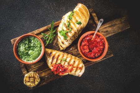 Grilled chicken breast with spicy sauces, tomatoes and herbs on dark rusty background copy space top view Stok Fotoğraf