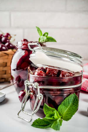 Homemade preserved cherry and mint jam, with fresh cherries on white marble background copy space