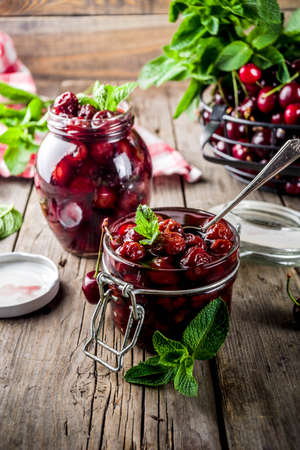 Homemade preserved cherry and mint jam, with fresh cherries on rustic old wooden background copy space