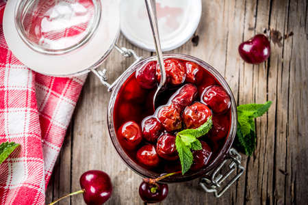 Homemade preserved cherry and mint jam, with fresh cherries on rustic old wooden background copy space above