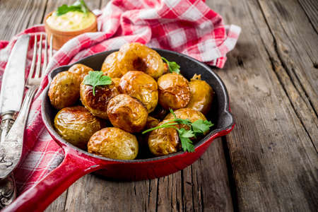 Baked in frying pan whole young potatoes, homemade vegetarian food, wooden old rustic table, with sauce, copy space Stok Fotoğraf