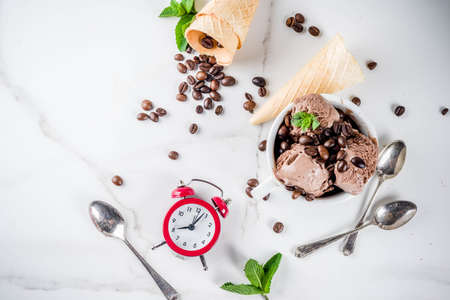 Time for coffee concept, with an alarm clock for hours in the frame. Homemade coffee ice cream, served with coffee beans and mint leaves, with ice cream cones, spoons. White marble background, above Stok Fotoğraf