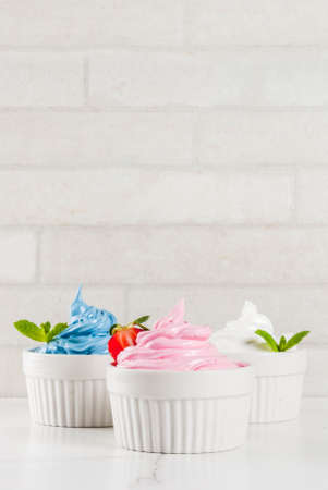 Healthy diet summer dessert, vanilla and berry frozen yogurt or  soft ice cream in white bowls, white marble background copy space