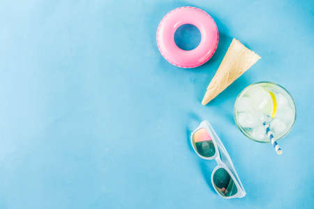 Summer holidays vacation concept background, hat, sunglasses, cooling drink (lemonade, mojito) with ice, ice cream cones, Lifebuoy blue background copy space flatlay above