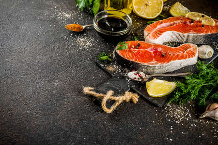 Raw salmon fish steaks with lemon, herbs, olive oil, ready for grill, slate cutting board, dark rusty background copy space