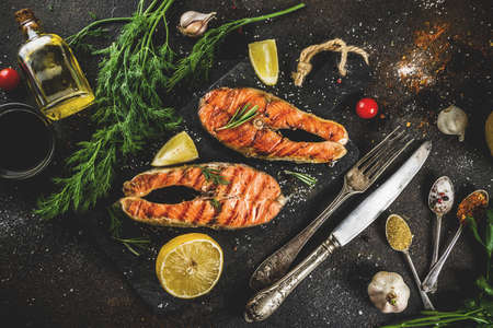 Grilled salmon fish steaks with ingredients lemon, herbs, olive oil, slate cutting board, dark rusty background copy space Stock fotó - 103112890