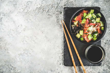 Asian trendy food, sushi poke bowl with cucumber, salmon, avocado, Black and White Sesame Seeds   Stock Photo