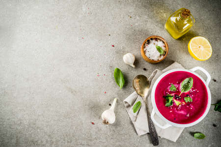 Vegan food, summer cold Beetroot gazpacho soup with lemon, avocado and fresh herbs copy space top view