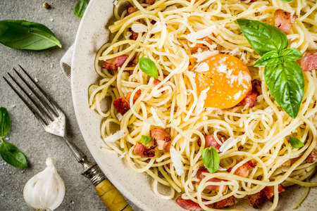 Traditional italian pasta, spaghetti carbonara with bacon, creamy sauce, parmesan cheese, egg yolk and fresh basil leaves grey stone background copy space Foto de archivo - 103190568