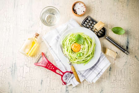 Trendy vegan food recipes, cheese zucchini spaghetti pasta with egg yolk with parmesan, olive oil and basil leaves, light concrete background copy space