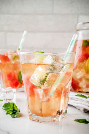 Iced watermelon and lime green tea with mint leaves, marble white background copy space Stock fotó