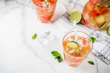 Iced watermelon and lime green tea with mint leaves, marble white background copy space Stock Photo