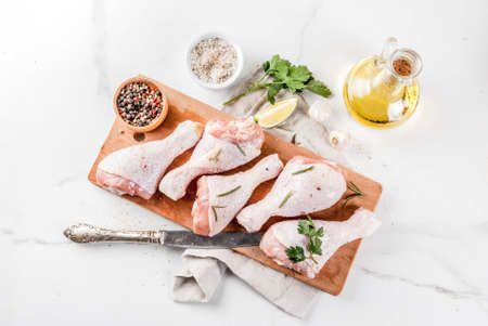 Raw meat, chicken legs, with olive oil, herbs and spices, on white marble background, copy space top view
