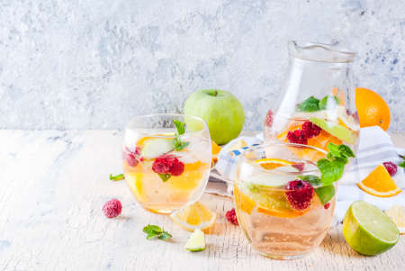 Summer cold cocktail, fruit and berry white sangria with apple, lemon, oranges and raspberry. light concrete background, copy space Stock Photo