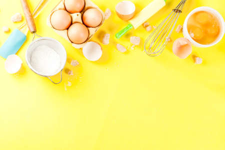 Ingredients and utensils for cooking baking egg, flour, sugar, whisk, rolling pin, on bright yellow background, copy space top view Stok Fotoğraf