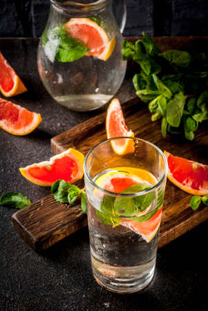 Summer refreshment detox water drink with Pink grapefruit and fresh mint, spa fruit water, lemonade or jin tonic cocktail, dark background copy space 写真素材 - 103925782