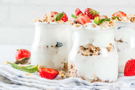Healthy summer breakfast idea, homemade layered parfe dessert in small jar with granola, yoghurt and strawberry, dark background copy space Stock Photo