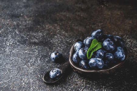 Raw fresh blueberries in small black bowl, dark rusty background copy space 스톡 콘텐츠