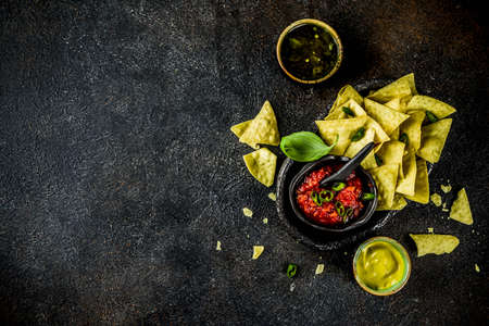 Mexican food, nachos snack with salsa and sauces on dark rusty background top view copy space