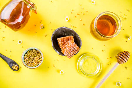 Organic floral honey, in jars, with pollen and honey combs, with wildflowers creative layout bright yellow background top view copy space 版權商用圖片