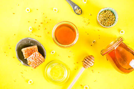 Organic floral honey, in jars, with pollen and honey combs, with wildflowers creative layout bright yellow background top view copy space Stock Photo