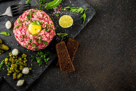 French cuisine, beef steak tartare with raw quail egg yolk, pickled cucumber and onions, fresh herbs, bread, dark rusty background copy space above
