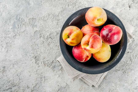 Raw fresh peaches in bowl on grey concrete background copy space above copy space