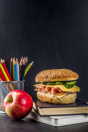Healthy school food concept, lunch with apple, sandwich, books and alarm clock on chalkboard background copy space Stok Fotoğraf