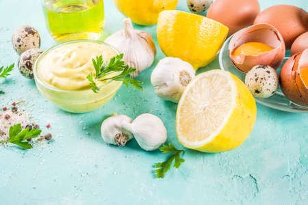 Homemade mayonnaise sauce with ingredients - lemon, eggs, olive oil, spices and herbs, light blue background copy space