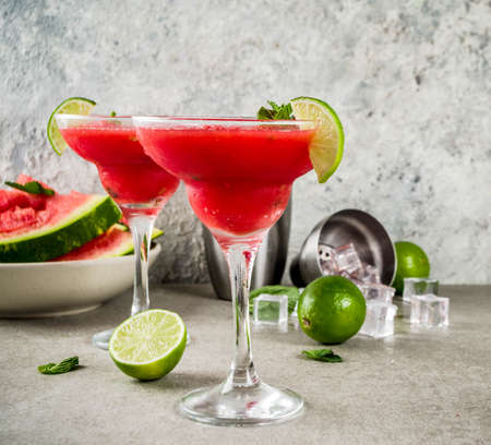 Watermelon margarita cocktail with lime and sliced watermelon, light concrete background copy space