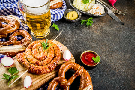 Oktoberfest food menu, bavarian sausages with pretzels, mashed potato, sauerkraut, beer bottle and mug, dark rusty background copy space Stock Photo