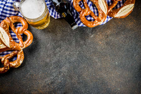 Oktoberfest food menu, bavarian sausages with pretzels, mashed potato, sauerkraut, beer bottle and mug, dark rusty background copy space top view