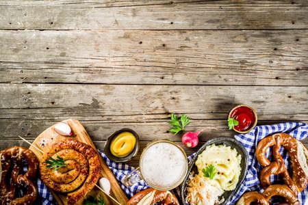 Oktoberfest food menu, bavarian sausages with pretzels, mashed potato, sauerkraut, beer bottle and mug old rustic wooden background, copy space above