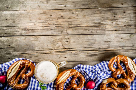 Oktoberfest food menu, bavarian pretzels with beer mug, old rustic wooden background, copy space above Stock Photo