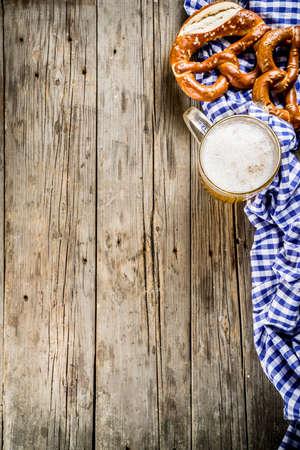 Oktoberfest food menu, bavarian pretzels with beer mug, old rustic wooden background, copy space above 写真素材