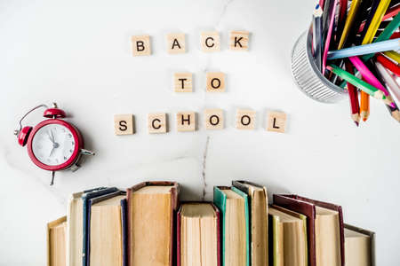 Back to school background with old books, alarm clock, pencils