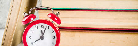 Back to school background with old books, alarm clock, pencils banner format