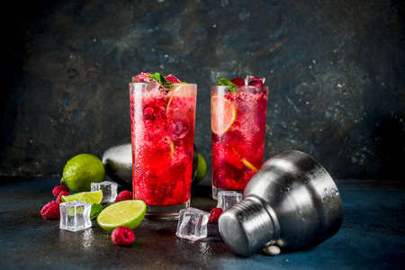 Iced summer drink cocktail, Raspberry and lime lemonade with fresh mint and lime, dark blue rusty background copy space Stock Photo