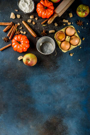 Sweet autumn baking cooking background with flour, rolling pin, decorative pumpkins, apples, cinnamon spices with anise cardamom sugar. Dark blue rusty background top view copy space