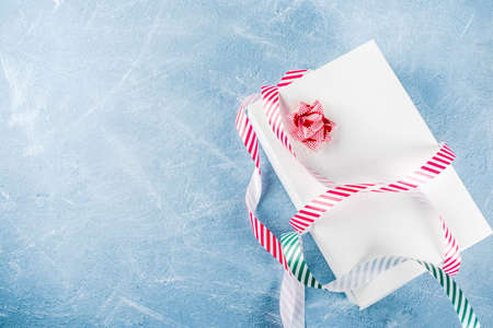 Christmas gift with festive ribbon on light blue background top view copy space